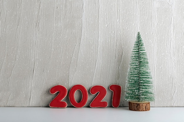 人工的なクリスマスツリーと赤い数字2021。新年のコンセプト。スペースをコピーします。
