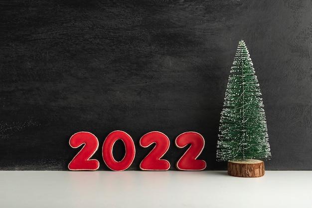 人工的なクリスマスツリーと黒の背景に赤い数字2022。新年のコンセプト。スペースをコピーします。