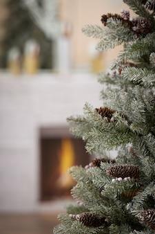 Искусственная елка с натуральными шишками, установленная дома для празднования рождества