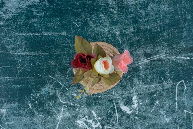 파란색 배경에 trivet에 점토 꽃병에 인공 화려한 장미.