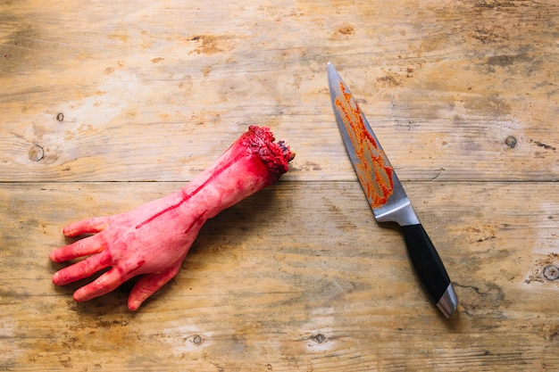Artificial cut hand in blood and knife