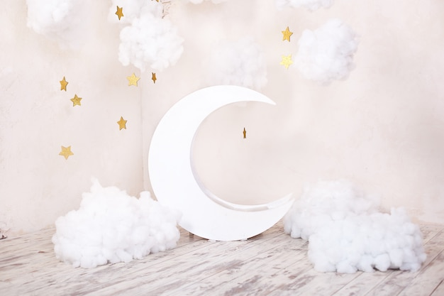 Artificial decorations with a moon and stars. vintage decorations. stylish vintage children's room with a wooden moon and textile clouds. vintage children's room with a moon.  scandinavian style room