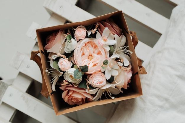 テーブルのクローズアップの紙箱に人工装飾花