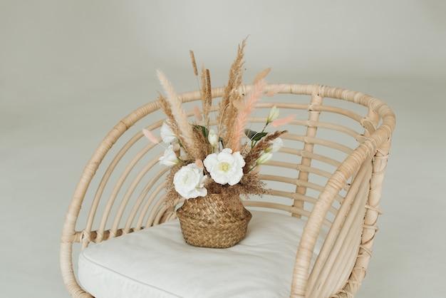 肘掛け椅子のクローズアップの籐のバスケットの人工装飾花