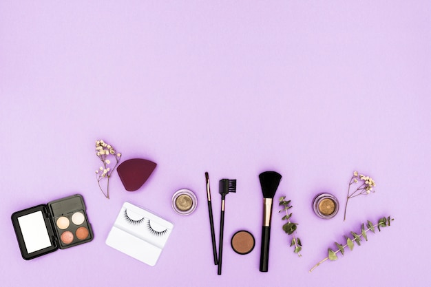 Artificial eyelashes; eyeshadow palette; blender; compact powder and makeup brushes with twig and gypsophila on purple background