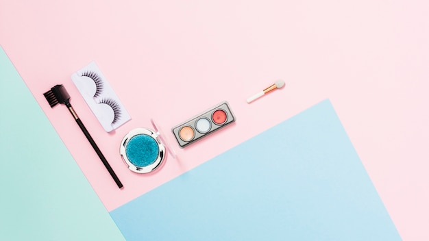 Artificial eyelashes; eyeshadow palette and makeup brush on triple colored background