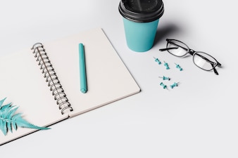 Artificial fern leaves and pen on white blank spiral notebook with coffee cup; eyeglasses and push pin