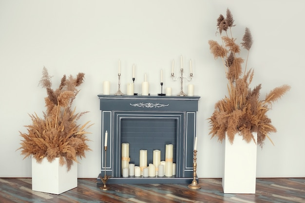 Artificial fireplace decorated with various decorative candles and dry decorative herbs