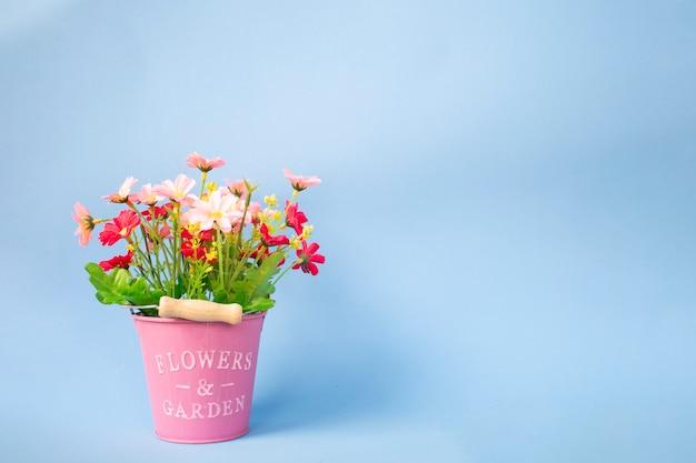 핑크 냄비와 파란색 배경에 인공 꽃 꽃다발