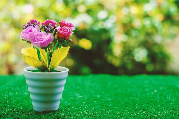 自然の背景がぼやけた緑の芝生の植木鉢の人工花