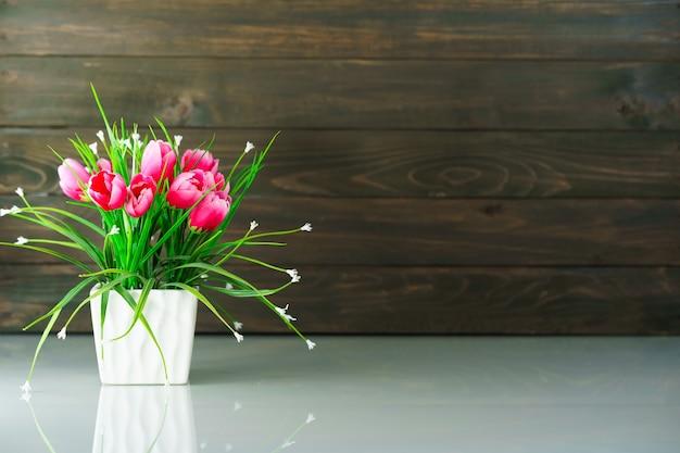 나무 벽 배경으로 테이블 위에 인공 꽃 꽃병 꽃다발