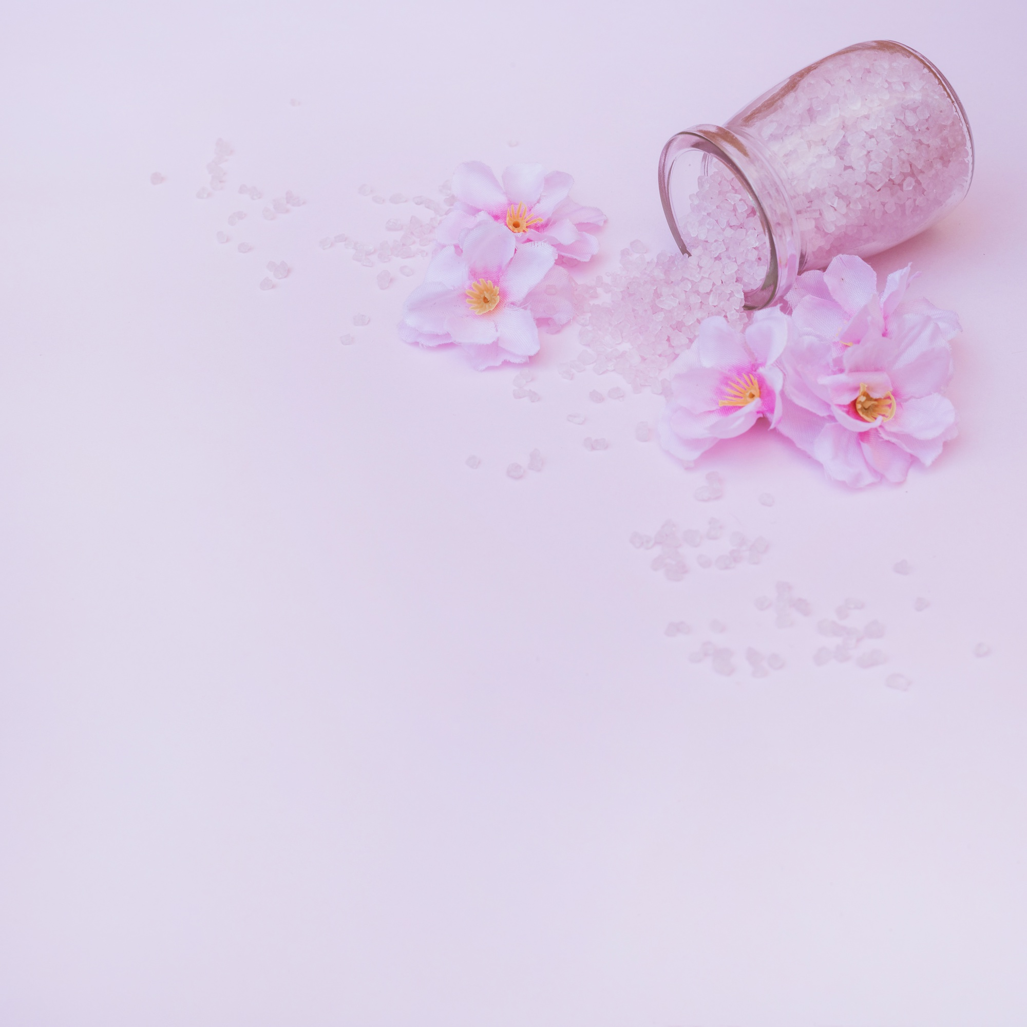 Artificial flowers and spilled salt from jar on pink background