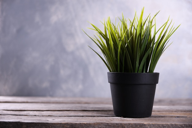 Artificial flowers grass different form in a pot on wooden table close up
