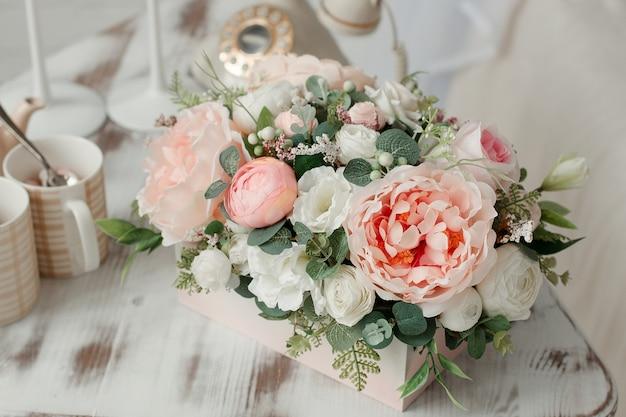 나무 상자에 인공 꽃입니다. 내부에 장식 꽃. 밝은 배경에 핑크 꽃입니다.