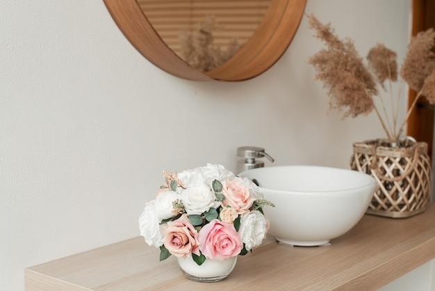 욕실 인테리어의 인공 꽃. 둥근 꽃병에 장식 꽃입니다. 둥근 꽃병에 인공 꽃. 화이트 욕실 인테리어. 장식 꽃.