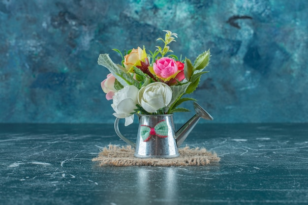 Artificial flowers in a watering can , on the blue background.