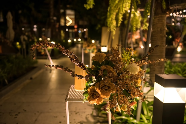 리조트 정원에서 야간 야외 결혼식에서 인공 황금 꽃과 촛불 장식.