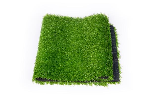 スポーツフィールドの人工芝、白い背景の上の緑のプラスチック製の草をクローズアップ。