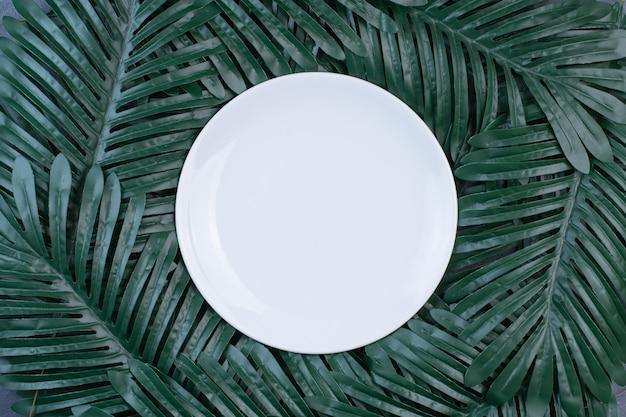 Искусственные зеленые листья вокруг белой пластины.