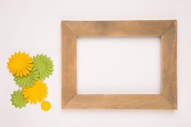 Artificial green and yellow flowers near the wooden empty frame on white backdrop