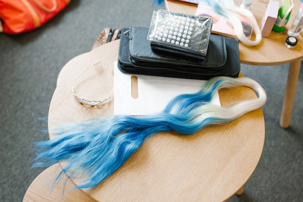 髪型を編むための青またはコーンフラワーブルー色の人工毛、編むためのアクセサリーの隣にある木製のテーブルの上に横たわる