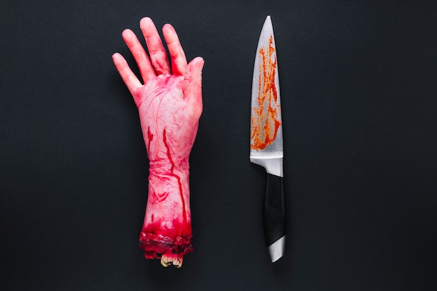 Artificial human hand in blood and knife