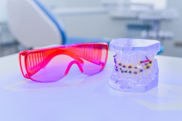 Artificial jaws with braces lie with glasses