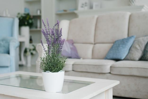 白いポットの人工ラベンダーの花は、家のリビングルームのコーヒーテーブルの上に立っています。