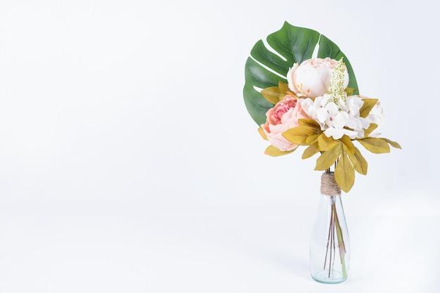 Foglia e fiori artificiali in vaso di vetro su bianco.