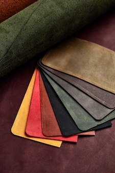Artificial leather samples on a cow leather background. top view.