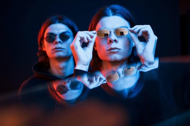 인공 조명. 쌍둥이 형제의 초상화입니다. 네온이있는 어두운 스튜디오에서 촬영 한 스튜디오