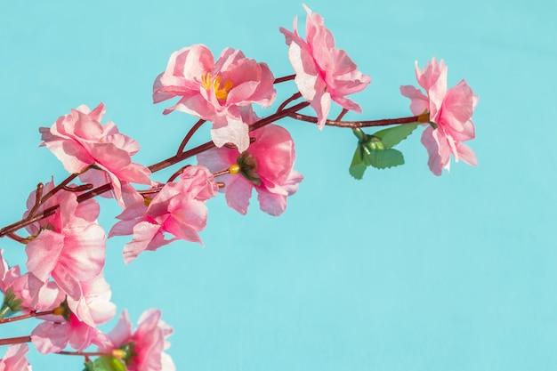 青い背景の上の人工ピンクの花。