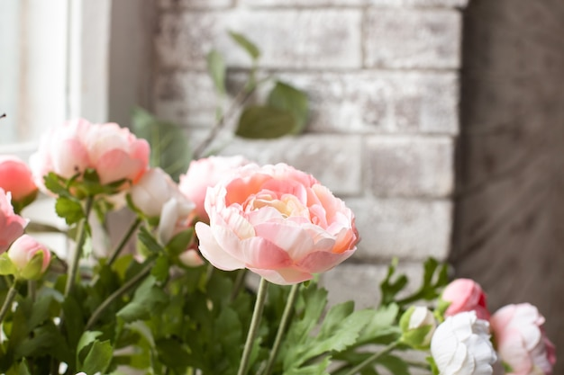Artificial pink flowers on white brick wall