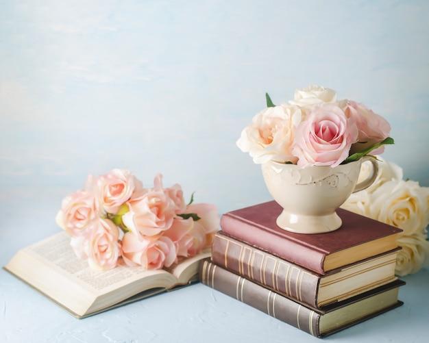 青の本とビンテージカップの人工のピンクのバラの花