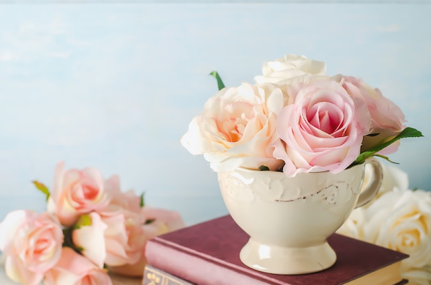 Artificial pink rose flowers in vintage cup with books on blue