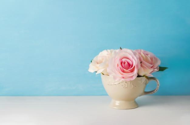 Artificial pink rose flowers in vintage cup