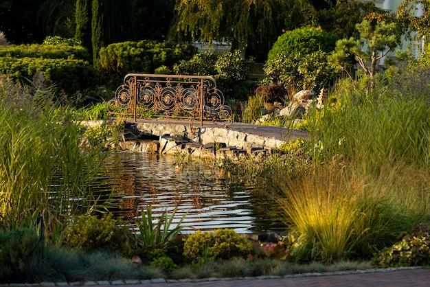 造園で飾られた茂みと低木のある人工池