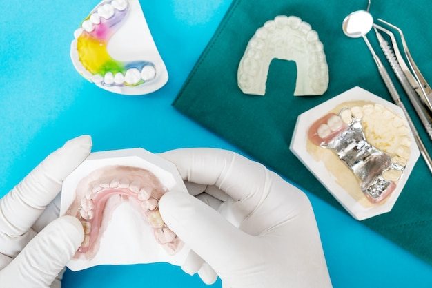 Artificial removable partial denture or temporary partial denture on blue ground.