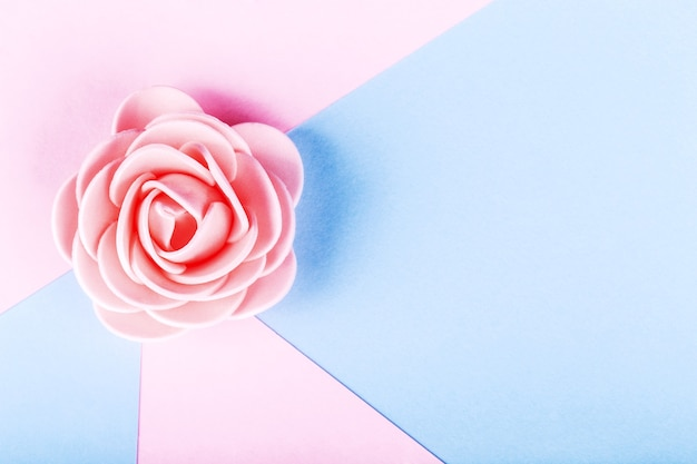 Artificial rose on a colored background, image with place for text