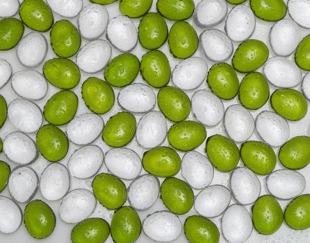 緑と白の色の水滴を持つ人工の丸い石、上面図。模造小石