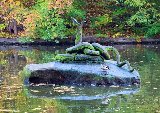 가을 공원에서 연못 센터에있는 돌에 인공 뱀