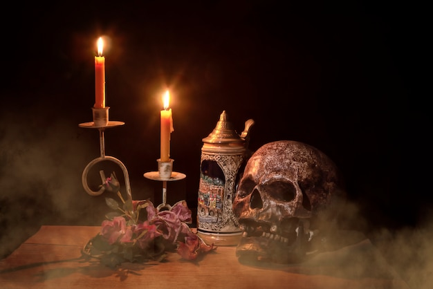 Artificial skull and candlestick on wooden layer on black background