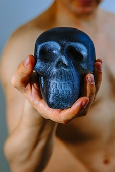 Artificial skull in the hand of a strong man