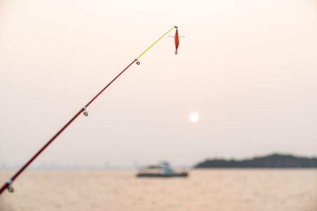 바다 배경으로 낚싯대에 인공 작은 물고기, 일몰 낚시.