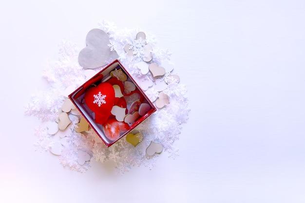 白い柔らかい背景の上のボックスに人工雪と赤い装飾的なハート。新年とクリスマスの装飾。