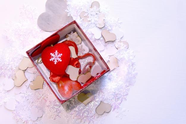白い柔らかい背景の上の赤いギフトボックスに人工雪と赤い装飾的なハート。新年とクリスマスの装飾。