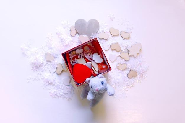 人工雪片、おもちゃの子猫、白い柔らかい背景に赤い装飾的なハート。新年とクリスマスの装飾。