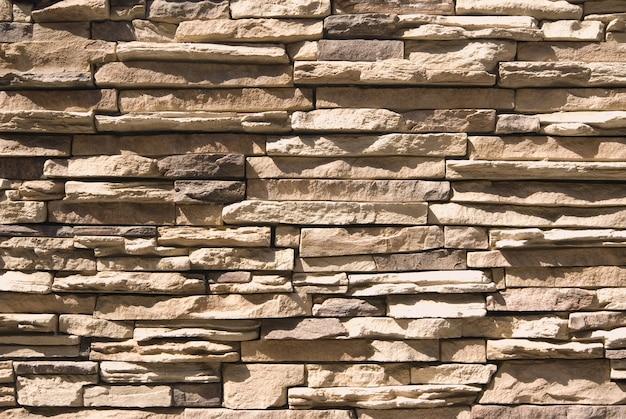 Искусственная каменная стена фон с ярким солнечным светом и тенями