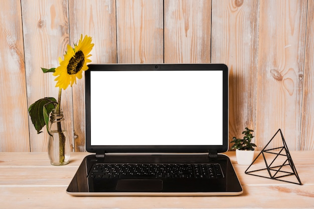 Artificial sunflower in vase with laptop on wooden table