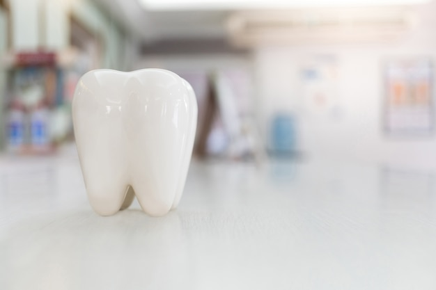 Artificial teeth model on wood table with blur background